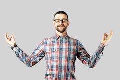 F?rdig ung man som poserar ?ver gr? bakgrund arkivfoto