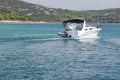 F?retaget av v?nner p? en liten motoryacht seglar l?ngs kusten n?ra en liten medelhavs- stad Vila p? vattnet i arkivfoto