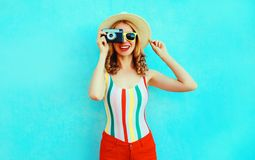 F?rgrik lycklig le ung kvinna som rymmer den retro kameran i sommarsugr?rhatten som har gyckel p? den bl?a v?ggen royaltyfri fotografi