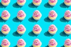 F?rgrik muffinmodell p? pastellf?rgad bl? bakgrund Id?rikt minsta partibegrepp royaltyfri foto