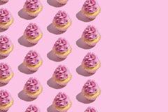 F?rgrik muffinmodell p? pastellf?rgad rosa bakgrund Id?rikt minsta partibegrepp arkivfoton