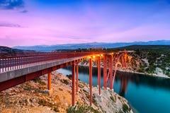 F?rgrik solnedg?ng ?ver den Maslenica bron i Dalmatia, Kroatien royaltyfria bilder