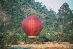 F?rgrik varmluftsballong som lyfter precis i tid att unders?ka h?rlig solnedg?ng ?ver Vang Vieng i Laos, South East Asia arkivfoto