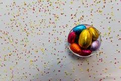 F?rgrika chokladeaster ?gg i en genomskinlig bunke med vit bakgrund och suddiga konfettier arkivbild
