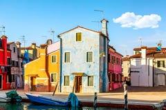 F?rgrika hus i Burano n?ra Venedig, Italien med fartyg och h?rlig bl? himmel i sommar Ber?md turist- dragning i Venedig royaltyfria bilder