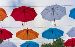 F?rgrika paraplyer i himlen Gatagarneringar från mångfärgade paraplyer royaltyfria bilder
