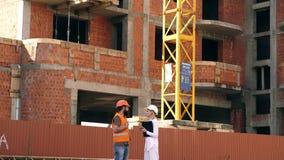 F?rh?llanden mellan konstruktionsklienter och deltagarebyggnadsbransch Kvinnatekniker och byggm?stare att meddela p? stock video