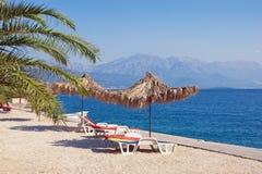 F?rias da praia do ver?o Paisagem de Sunny Mediterranean com guarda-chuvas de praia Montenegro, ba?a de Kotor foto de stock royalty free