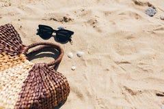 F?rias de ver?o Óculos de sol e saco à moda da palha no Sandy Beach com escudos do mar Acess?rio da menina na praia Ol?! ver?o fotos de stock