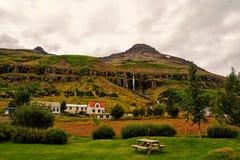 F?rias de ver?o Aldeia da montanha da viagem e do desejo por viajar no c?u nebuloso em Sejdisfjordur, Isl?ndia Casas de campo sob fotografia de stock