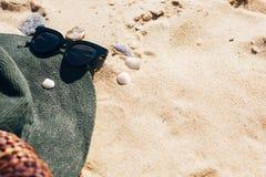 F?rias de ver?o Chapéu, óculos de sol e saco à moda da palha no Sandy Beach com escudos do mar Acess?rio da menina na praia Ol?!  foto de stock royalty free