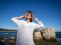 F?rias no mar: Uma menina nos ?culos de sol e uma palha transformam em um litoral rochoso em um dia ensolarado brilhante Desolado imagem de stock