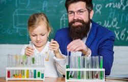 F?rklaring av kemi f?r att lura Hur man intresserar barn f?r att studera Fascinera kemikurs Lärare och elev för man skäggig arkivfoto