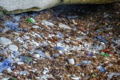 F?rorenad kustlinje med plast-, polyetylen, plast- flaskor och avfall, milj?fr?gor, massiv f?rorening av arkivbild