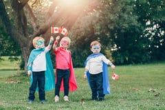 F?rskole- Caucasian barn som spelar superheroes arkivbild
