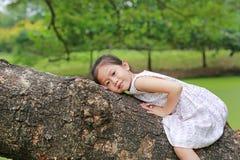 F?rtjusande flickakl?ttring f?r litet barn och vila p? den stora tr?dstammen i den utomhus- tr?dg?rden royaltyfri bild