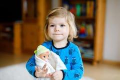F?rtjusande gullig liten litet barnflicka som spelar med dockan Lyckligt sunt behandla som ett barn barnet som har gyckel med rol royaltyfri bild