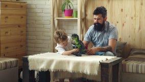 F?rtjusande lekar f?r litet barn med hans sk?ggiga fader med plast- dinosaurier Son- och faderlek i stridkamp mellan lager videofilmer