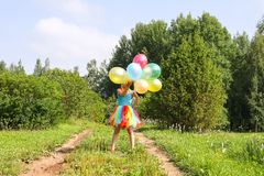 F?rtjusande liten flicka p? gr?nt gr?s med f?rgrika ljusa ballonger fotografering för bildbyråer