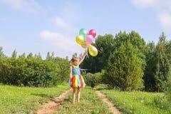 F?rtjusande liten flicka p? gr?nt gr?s med f?rgrika ljusa ballonger royaltyfria foton