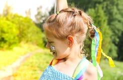 F?rtjusande liten flicka p? gr?nt gr?s med f?rgrika ljusa ballonger arkivfoton
