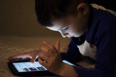 F?rtjusande pys som spelar p? en digital minnestavla Pojke som ser den digitala minnestavlan F?r?ldra- till?telsebegrepp, s?kerhe arkivbilder