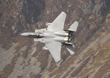 F15 Low Level. An F15 Eagle travels low and fast through a valley on a mission stock image