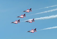 F16 in formation. Five red and white F16 fighter aircrafts flying in formation with white smoke trailing Royalty Free Stock Photos