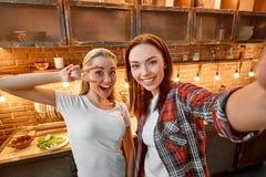 Faça a amizade para dobrar suas alegria e felicidade Amigos fêmeas novos na cozinha moderna que prepara junto o vegetariano imagens de stock royalty free