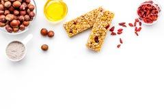 Faça barras de granola entusiastas com farinha de aveia, porcas, mel e bagas Espaço branco da cópia da opinião superior do fundo imagens de stock royalty free