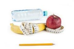 Faça dieta, comer saudável, alimento e pese o conceito da perda - próximo acima da maçã da banana e da fita de medição fotos de stock