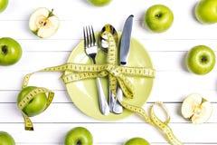 Faça dieta o ajuste da tabela do conceito com cutelaria, a fita de medição amarela e as maçãs verdes na tabela de madeira branca foto de stock