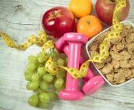 Faça dieta o conceito da aptidão - pesos, fita de medição, flocos e frutos frescos na tabela de madeira Imagens de Stock
