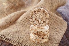 Faça dieta a pilha dos bolos de arroz na tabela de madeira coberta com o guardanapo homespun, foco seletivo Imagens de Stock