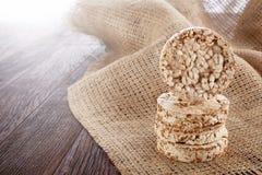 Faça dieta a pilha dos bolos de arroz na tabela de madeira coberta com o guardanapo homespun, foco seletivo, luminoso Fotografia de Stock Royalty Free