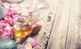 Faça massagens o óleo, as flores das pétalas e as pedras do zen Fotografia de Stock Royalty Free