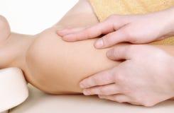 Faça massagens os braços de uma mulher nova Foto de Stock Royalty Free