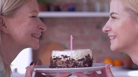 Faça o desejo no aniversário, o mum feliz com velas de sopro da filha adulta no bolo do feriado e os sorrisos e olhe se