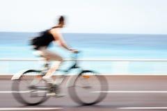 Faça sinal ao ciclista borrado que vai rapidamente em uma pista da bicicleta da cidade Fotos de Stock Royalty Free
