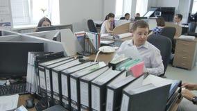 Faça sinal ao longo do escritório ocupado moderno com trabalhadores profissionais