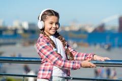 Faça sua criança feliz com os melhores fones de ouvido avaliados das crianças disponíveis agora A criança da menina escuta música fotografia de stock