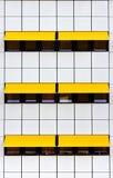 Façade avec les tuiles blanches et les tentes jaunes Image stock