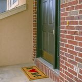 Façade carrée d'une maison avec un petit porche et un mur de briques rouge classique image stock