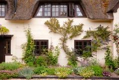 Façade couverte de chaume anglaise traditionnelle de maison avec la décoration de fleur photo libre de droits
