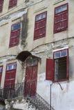 Façade d'un vieux bâtiment avec les portes et les fenêtres en bois rouges Photo libre de droits