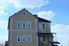 Façade d'une grande maison brune avec des fenêtres contre le ciel et les nuages Images libres de droits