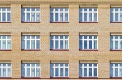 Façade de brique de la maison avec les fenêtres blanches Photo stock
