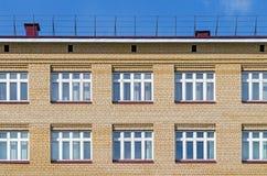 Façade de brique de la maison avec un toit et des fenêtres blanches contre le ciel bleu Photos stock