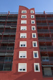Façade rouge avec les fenêtres et les balconys blancs Photos libres de droits