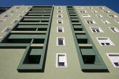 Façade légère et vert-foncé avec des balcons et des fenêtres blanches Image stock